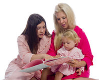 Mother and Daughters Reading  a Book Stock Photo