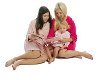 Mother with Daughters Reading a Book Stock Photo