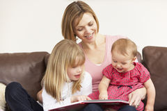 Mother And Daughters Reading Book. Together Royalty Free Stock Image