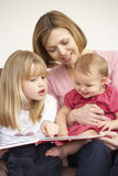 Mother And Daughters Reading Book. Together Royalty Free Stock Images