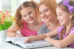 Mother with  daughters reading. Portrait of mother with daughters reading book Royalty Free Stock Images