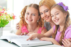 Mother with  daughters reading Stock Image