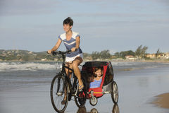 Mother and daughters riding a bike on the beach. Stock Photos