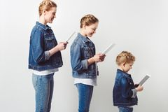 Mother and daughters in similar denim clothing standing in row and using tablets. On grey stock images