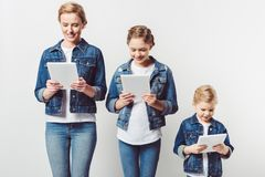 Mother and daughters in similar denim clothing standing in row and using tablets. On grey stock photography