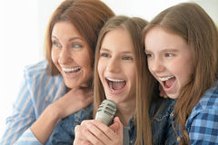 Mother and daughters singing karaoke. Portrait of happy mother and daughters singing karaoke Stock Photography