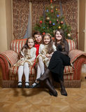 Mother with daughters sitting on sofa at christmas eve Royalty Free Stock Photo
