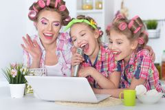 Mother and daughters making hairstyles. Mother and daughters sitting at table with laptop and singing karaoke Stock Photography