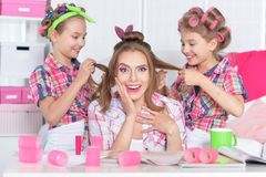 Mother and daughters making hairstyles. Mother and daughters sitting at table and making hairstyles Stock Photo