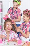 Mother and daughters making hairstyles Royalty Free Stock Photography