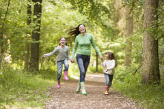 Mother and daughters skipping on path smiling Stock Photo