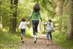 Mother and daughters skipping on path smiling Royalty Free Stock Image