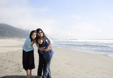 Mother and daughters smiling on beach Stock Image