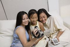 Mother and Daughters on sofa looking at Video Camera screen Stock Image