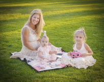 Mother and Daughters Tea Party Celebration. A mother and her two young daughters, all with blond hair and blue eyes, and in their party dresses,  sit on a Stock Images