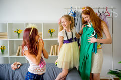 Mother and daughters try clothes Stock Photos