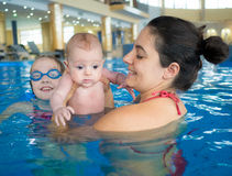 Mother and daughters. Mother with two daughters having fun in the pool on family holidays Stock Photos