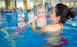Mother and daughters. Mother with two daughters having fun in the pool on family holidays Stock Photo