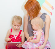 Mother and daughters using pc. Royalty Free Stock Image