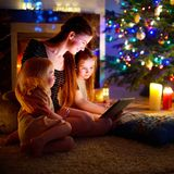 Mother and daughters using a tablet by a fireplace on Christmas Royalty Free Stock Images