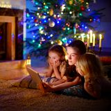Mother and daughters using a tablet by a fireplace on Christmas Royalty Free Stock Photo