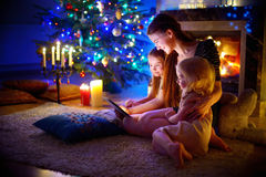 Mother and daughters using a tablet by a fireplace on Christmas Royalty Free Stock Photography