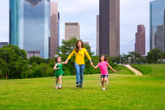 Mother and daughters walking holding hands on city skyline. Mother and daughters walking holding hands on modern city skyline over park green lawn Royalty Free Stock Images