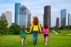 Mother and daughters walking holding hands on city skyline Royalty Free Stock Images