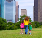 Mother and daughters walking holding hands on city skyline. Mother and daughters walking holding hands on modern city skyline over park green lawn Royalty Free Stock Image