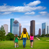 Mother and daughters walking holding hands on city skyline Stock Images