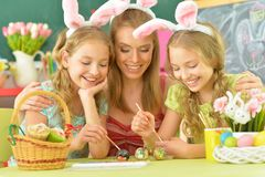 Mother with daughters wearing rabbit ears decorating Easter eggs. At home stock photography