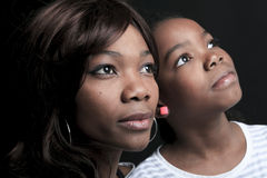 Mother and daughtler look away over black Royalty Free Stock Photos