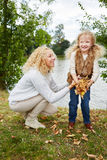 Mother and daugther collecting leaves stock photo