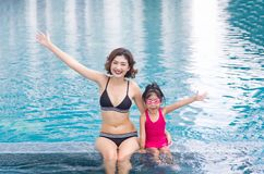 Mother and daugther love to swim together on swimming pool. Happy on vocation day Stock Photo