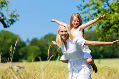 Mother with daugther in meadow Stock Photos