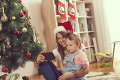Watching cartoons. Mother and daugther sitting on the floor next to a Christmas tree, watching cartoons on a smart phone. Focus on the mother stock image