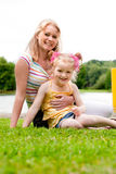 Mother and daugther sitting on the grass Stock Images