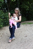 Mother with daugther on swing Stock Images