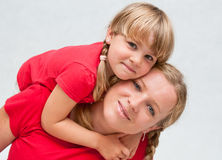 Mother with dauther together. A mother lifting her daughter on her back Royalty Free Stock Images