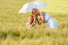 Mother and dauther under white umbrella Royalty Free Stock Image