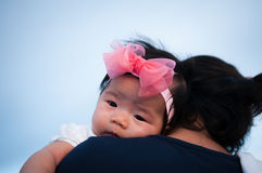 Mother day bonding concept with newborn baby nursing. Mother is holding newborn baby with flower pink headband with blue sky. Focu. S at infant girl Royalty Free Stock Images