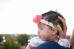 Mother day bonding concept with newborn baby nursing. Mother is holding newborn baby with flower pink headband with blue sky. Focus at infant girl Royalty Free Stock Images