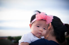 Mother day bonding concept with newborn baby nursing. Mother is holding newborn baby with flower pink headband with blue sky. Focus at infant girl Royalty Free Stock Photos