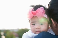 Mother day bonding concept with newborn baby nursing. Mother is holding newborn baby with flower pink headband with blue sky. Focus at infant girl Royalty Free Stock Image