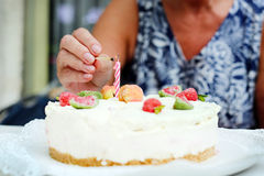 Mother day, celebrating birthday, lighting a candle on a cake Stock Image