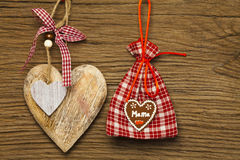 Mother day decoration. A big wooden heart and a red white checkered jute gift sack on old wooden board Stock Photos