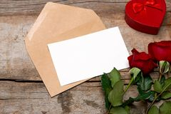 Mother Day. Rose and blank paper in envelope on wooden background.  royalty free stock images