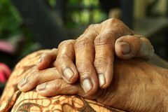 Wrinkled hands folded on lap closeup. royalty free stock photos