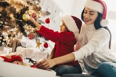 Mother decorating Christmas tree with her daughter stock photos