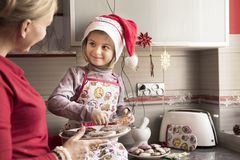 Mother decorating cookies with her little daughter royalty free stock photography